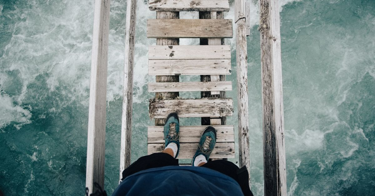 photo of a person's legs standing on a rickety bridge with rapid water underneath
