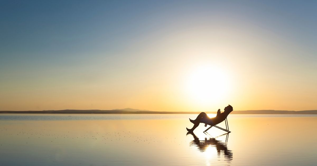 photo shows a silhouette of a lone man reclining in a deck chair on a beach at sunrise