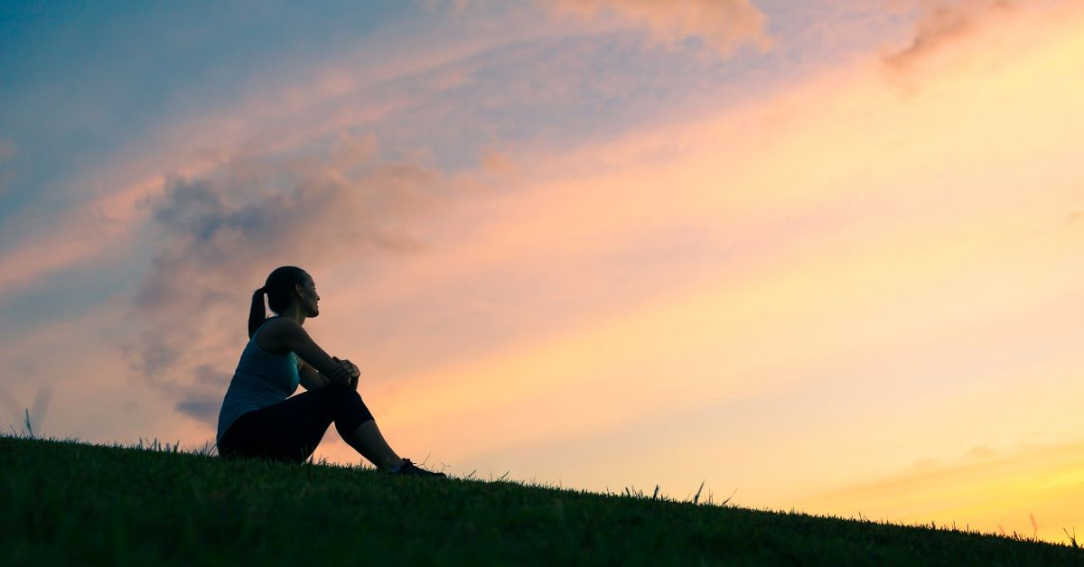 photo of a woman's profile silhouette as she sits on a hill with a sunset behind her