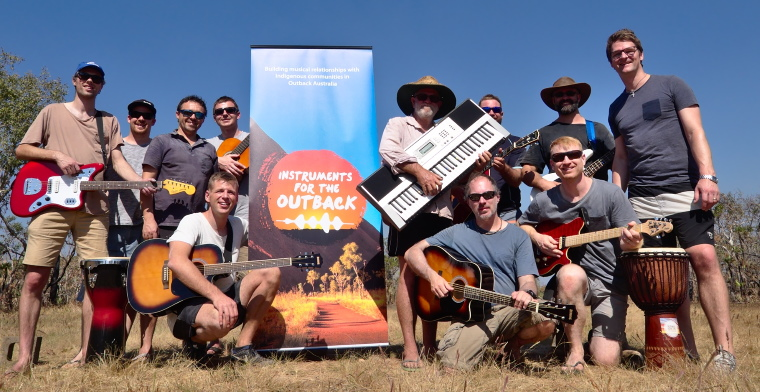 christian musicians posing with instruments in front of a banner for instruments for the outback