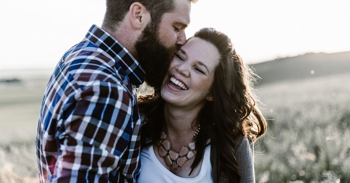photo depicts a man kissing a woman on the side of her head as she laughs happily
