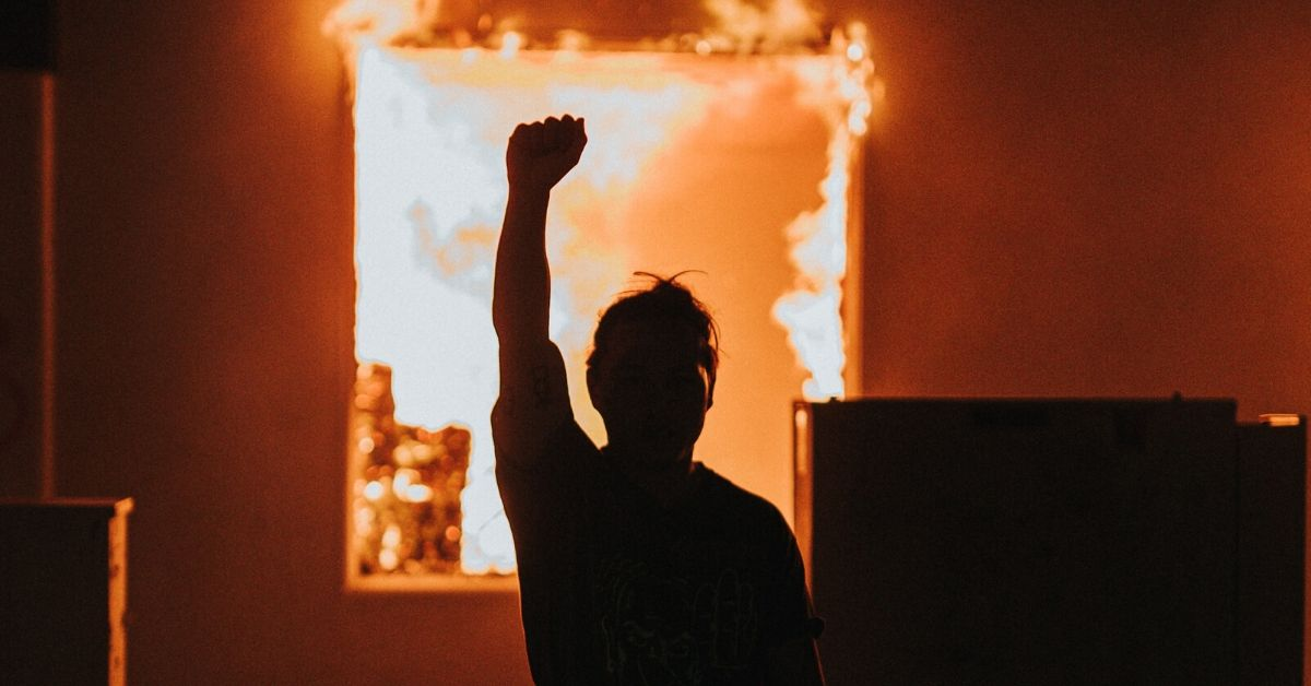 photo depicts a silhouette of a person with their fist raised in front of a fire