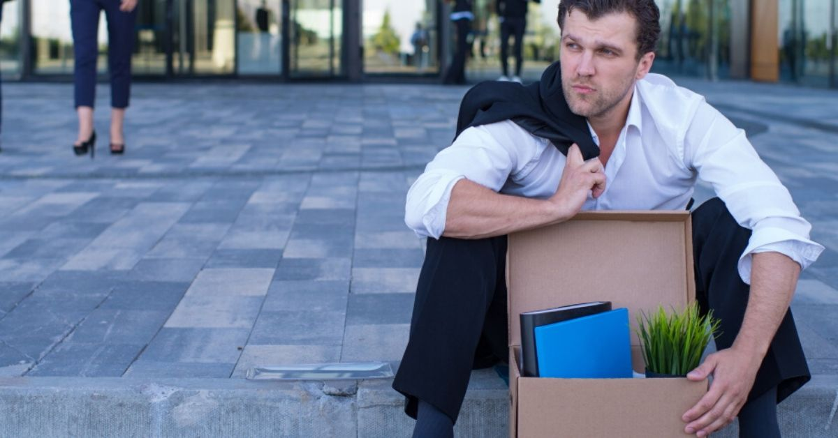 photo of a well dressed man sitting on the side of the road wth a box of belongings