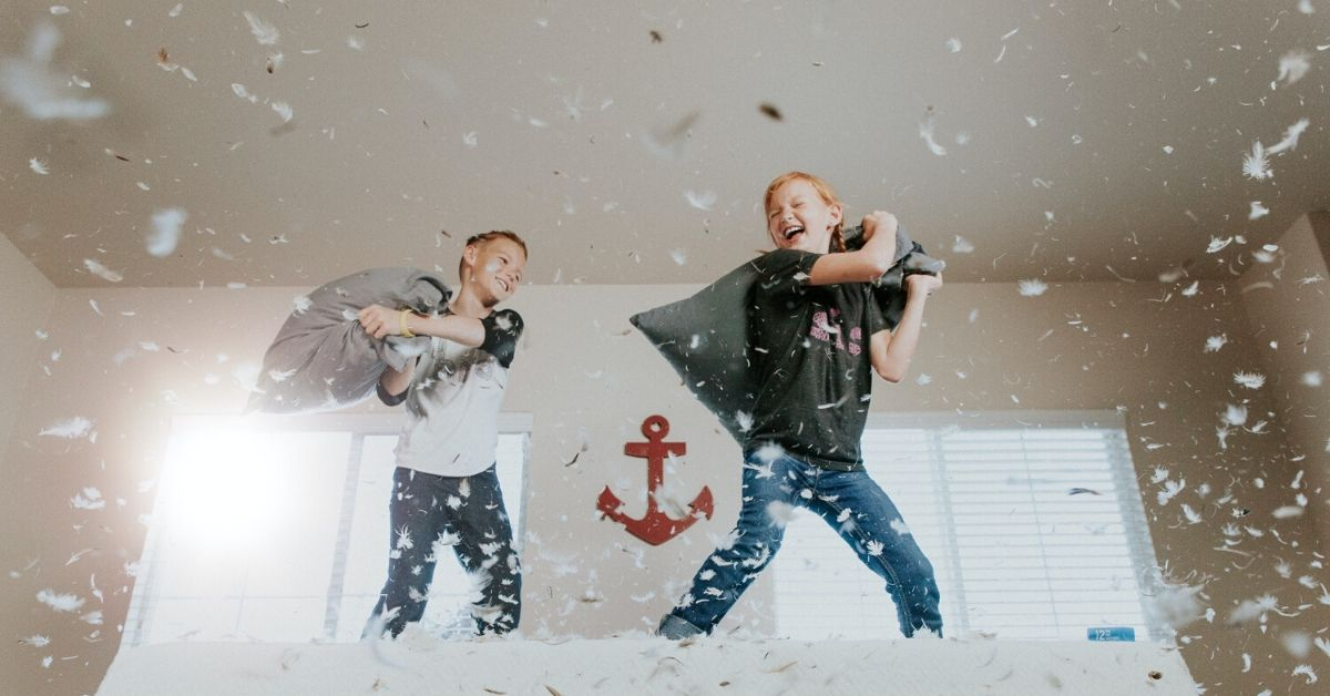 photo shows two kids having a pillow fight has feathers rain down around them