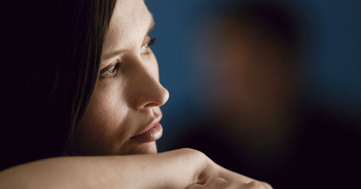 woman resting chin on her arm looking contemplative