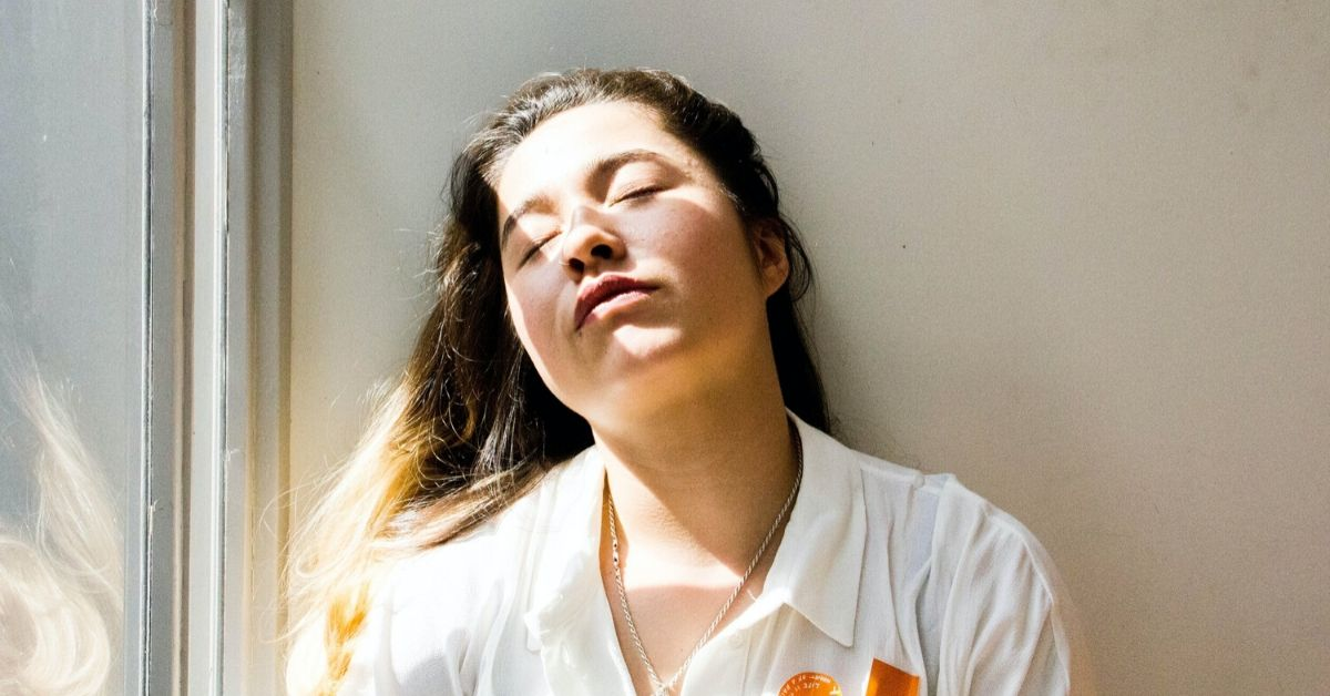 girl with eyes closed leaning against a wall as sunlight spills over her face