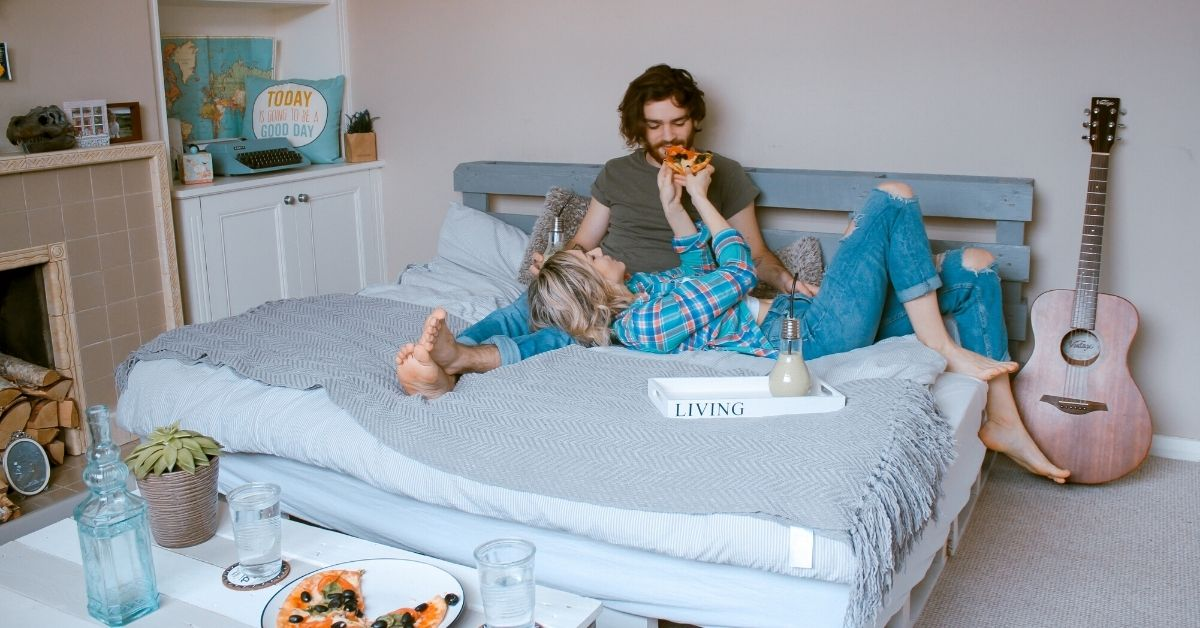 girl feeds her boyfriend pizza on a bed