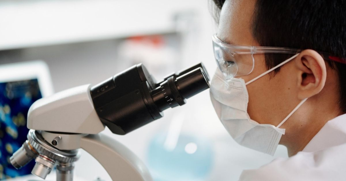 man wearing mask look through a microscope in laboratory