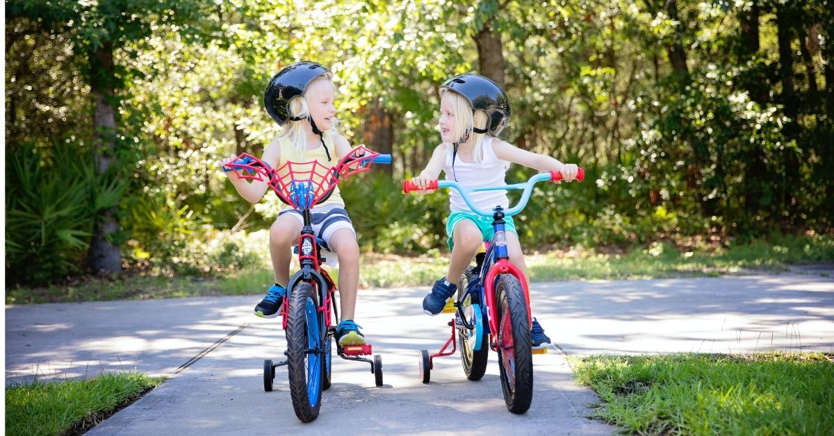 two young girls riding bikes with training wheels
