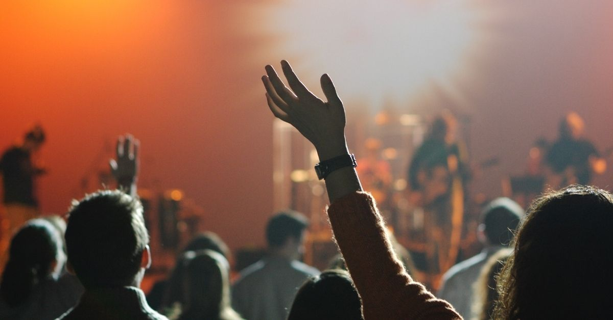 a person with raised hands in a church service