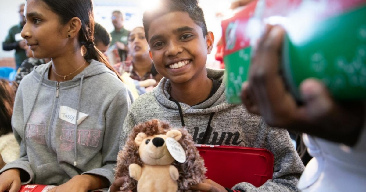 smiling children holding shoeboxes filled with gifts