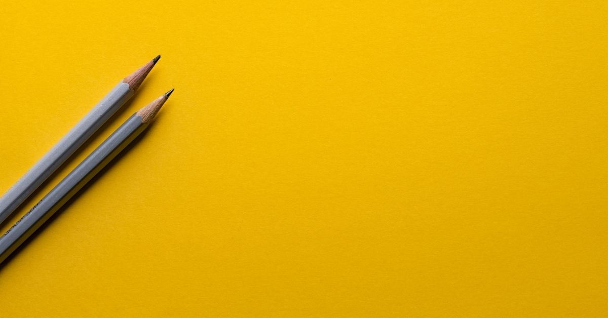 two pencils on a yellow background