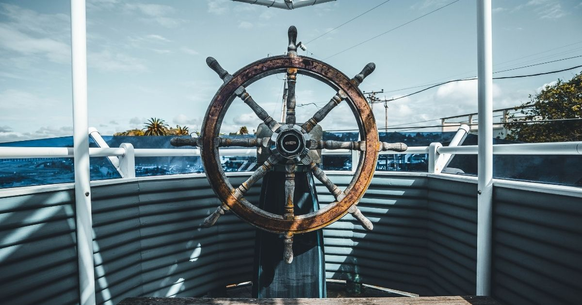 a wooden steering wheel on a boat overlooks blurry water