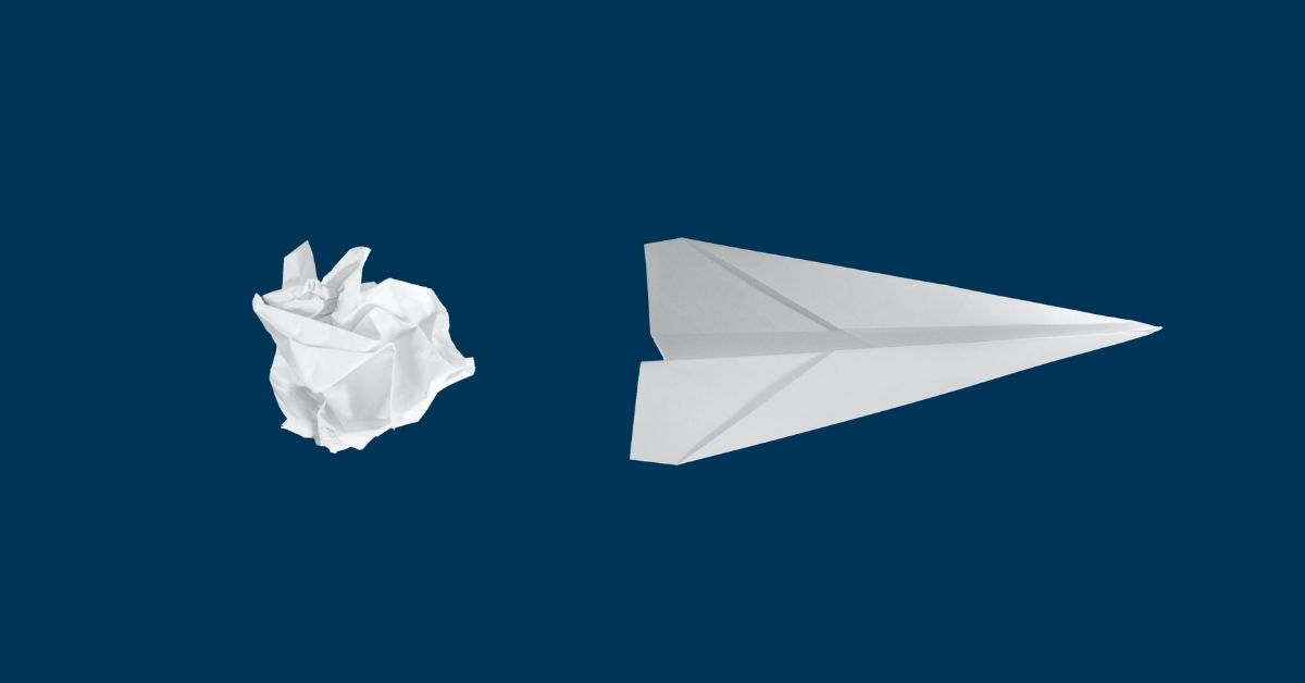 a paper plane beside a crumpled ball of paper
