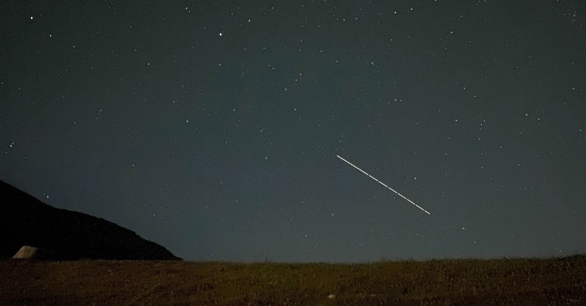 shooting star on a dark night over a field