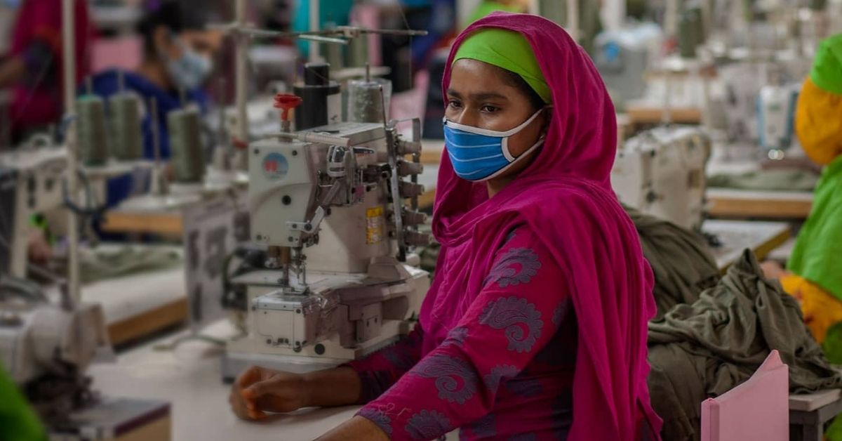 a female worker stands beside a sewing machine wearing a mask