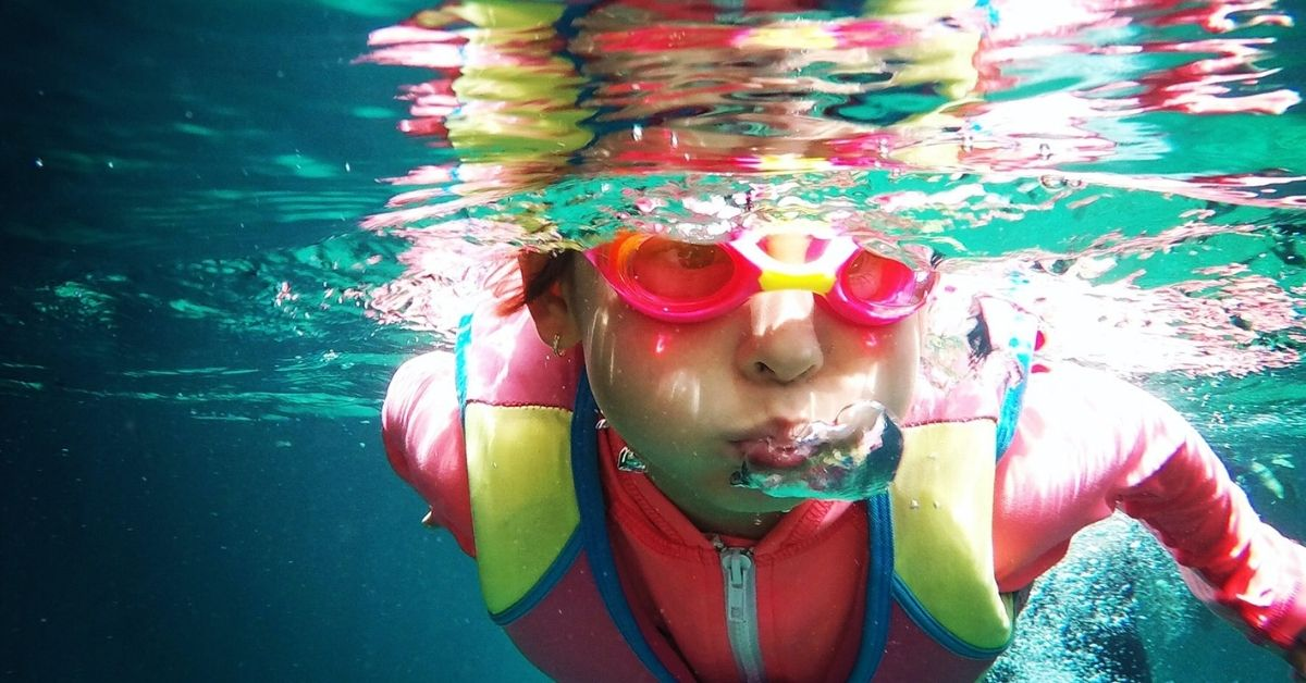 underwater shot of kid swimming wearing goggles and swimming cap
