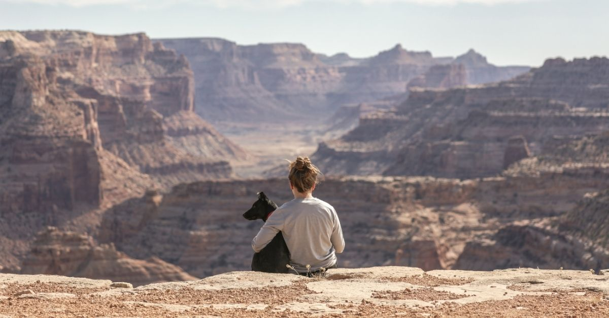 woman and her dog sitting looking out over mountain range