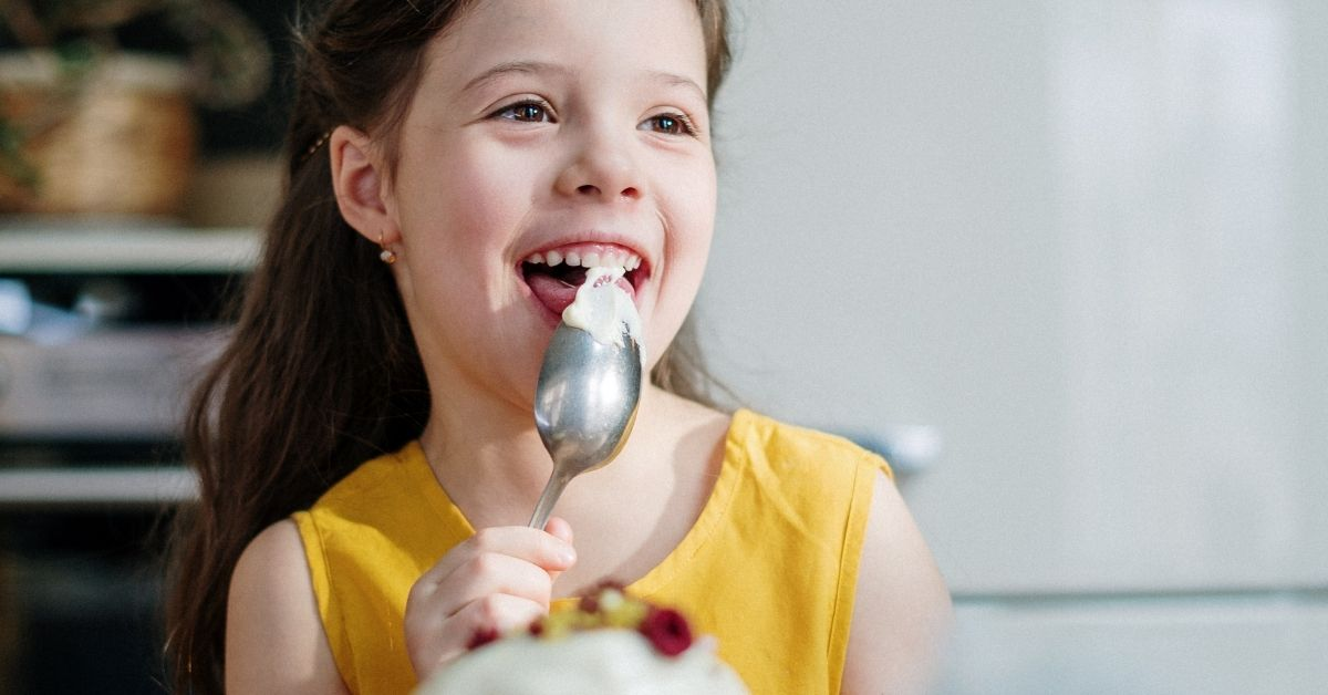 girl smiling licking a spoon