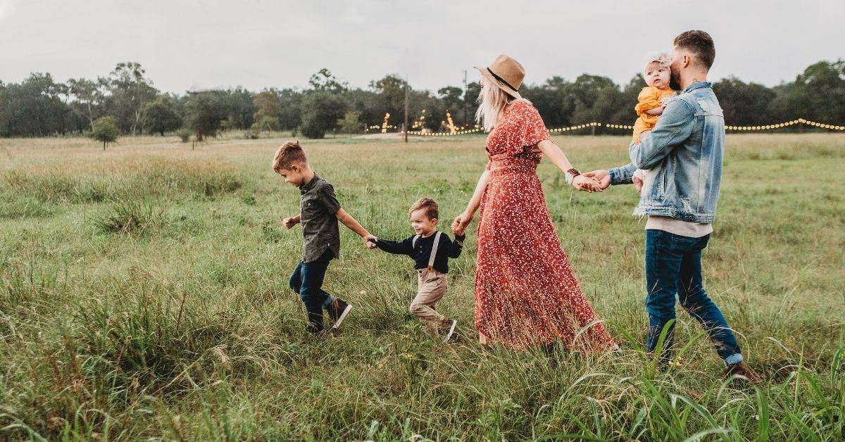 perfect model family holding hands walking through a field