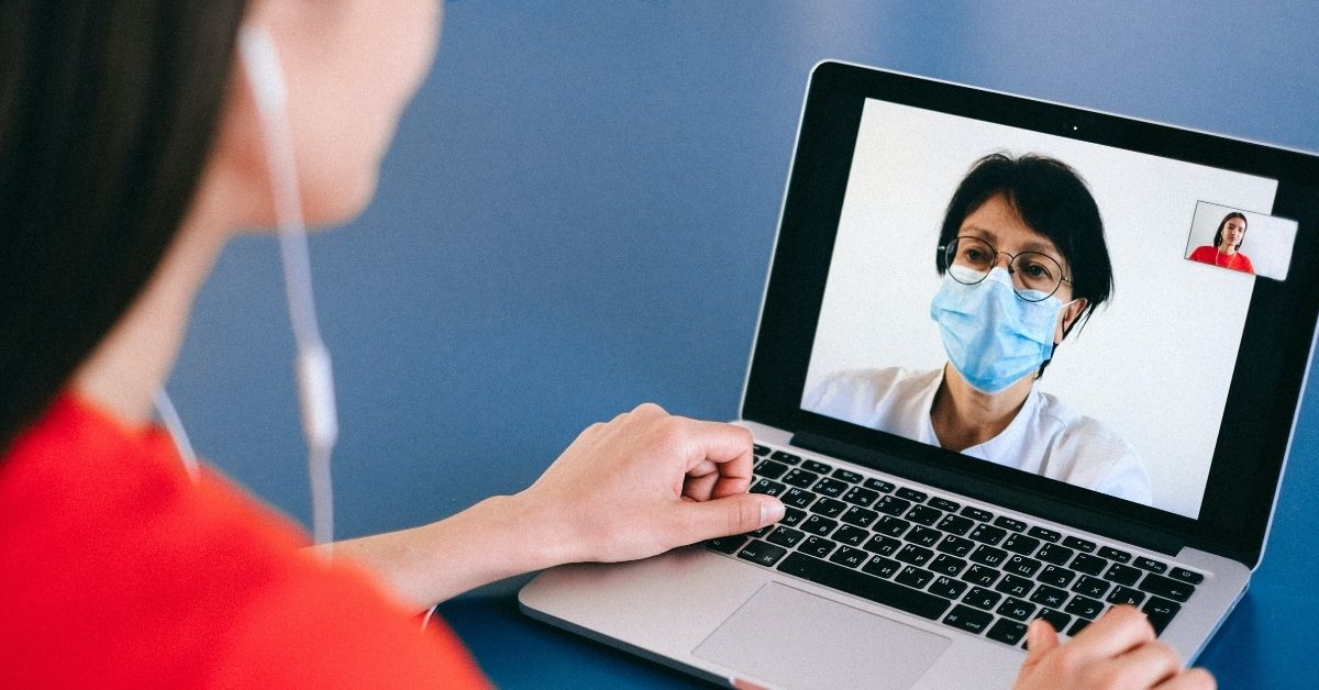 a woman video chats with a doctor on her computer