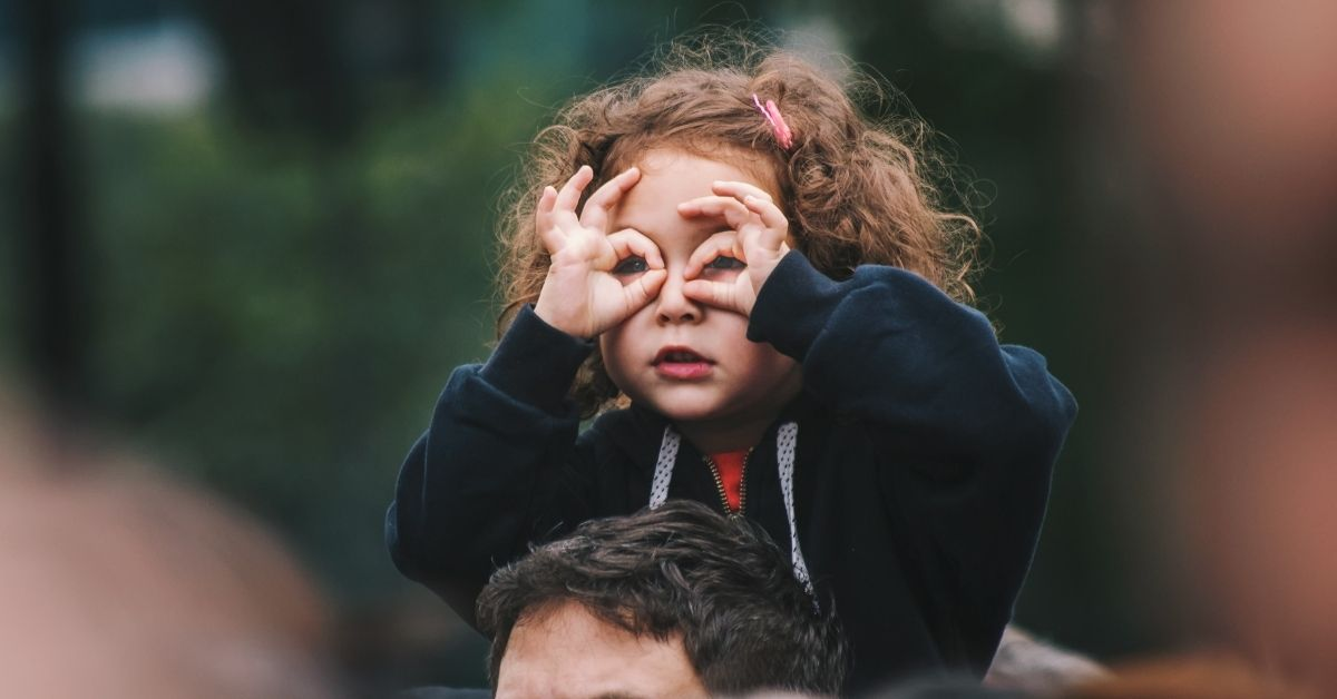 young girl forming glasses over her eyes with her hands
