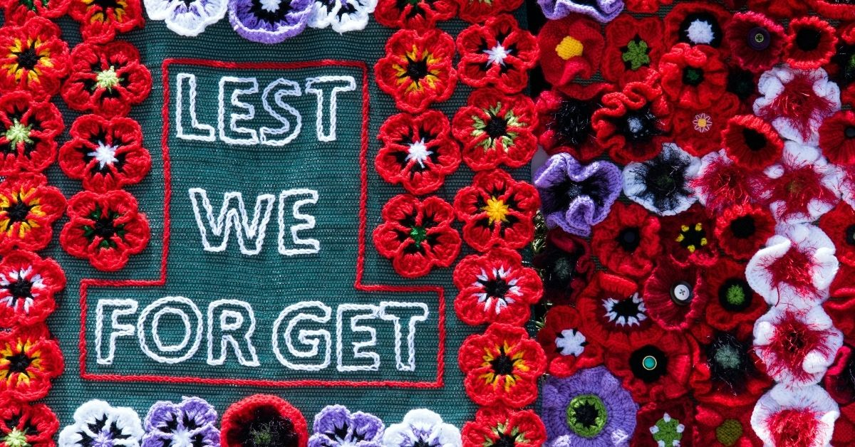 "a knitted banner of poppies and wording ""lest we forget"""