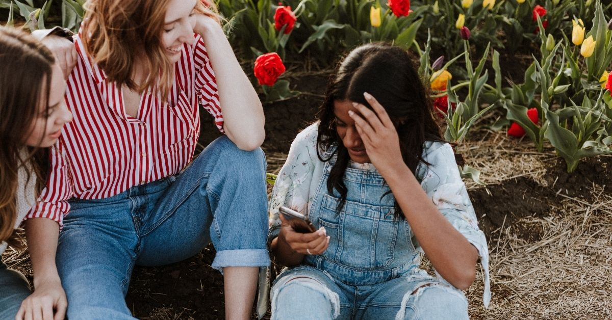 a group of friends sit on the ground together looking down at a phone