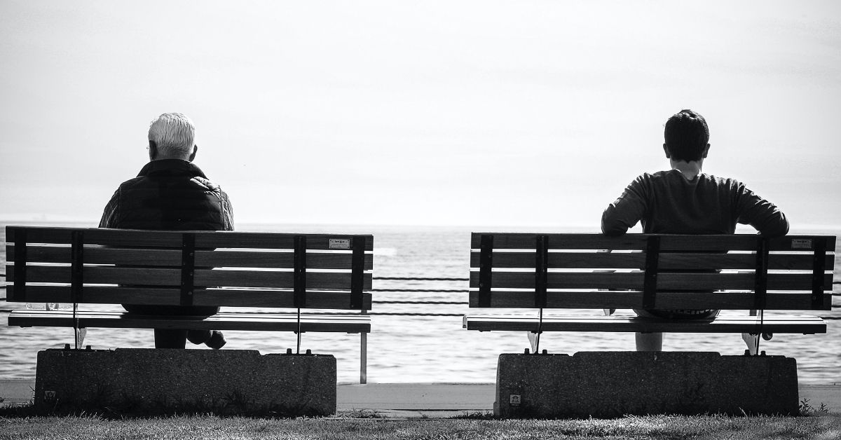 two men sitting on separate park benches gazing forward