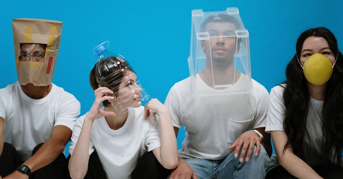 a conceptual photo of people wearing white shirts wearing masks made out of products such as a paper bag, bucket and cut in half plastic bottle posing in front of a blue backdrop