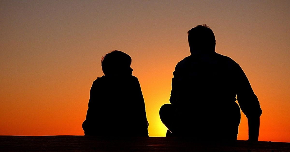 the silhouette of a father and son sitting on the ground talking from behind