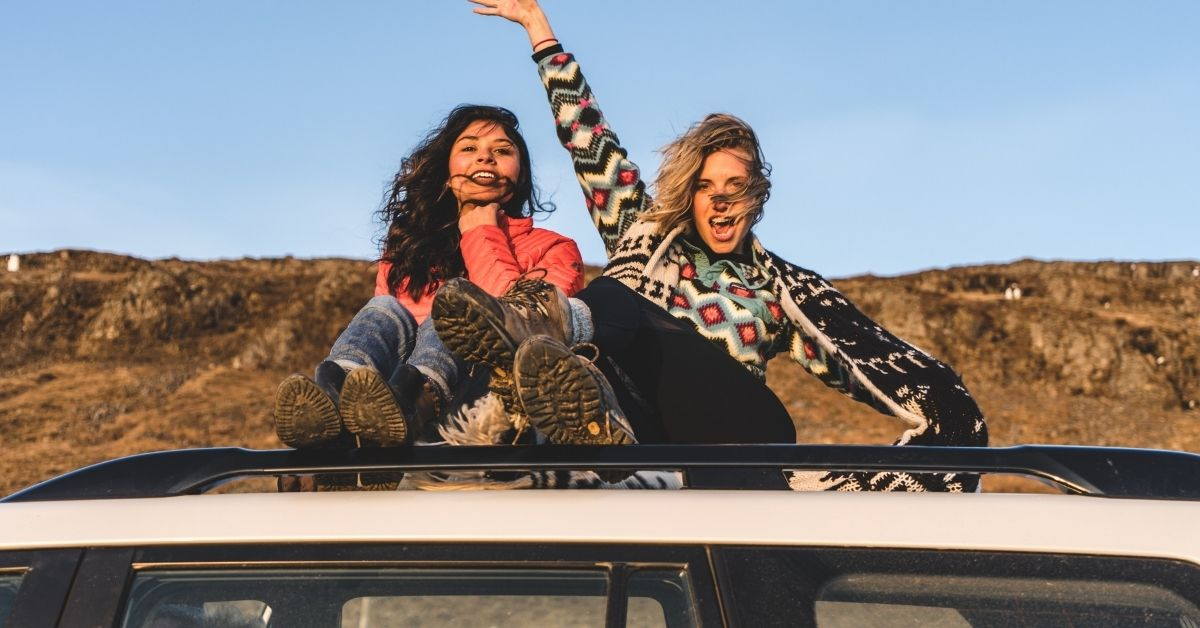 two girls on a roadtrip sitting on top of a car