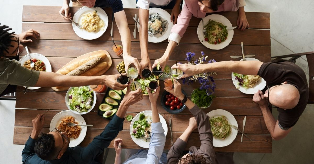 a large diverse family share a meal around a lunch table