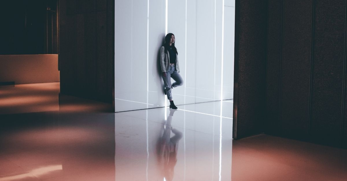a girl leans against a wall, alone in a big room