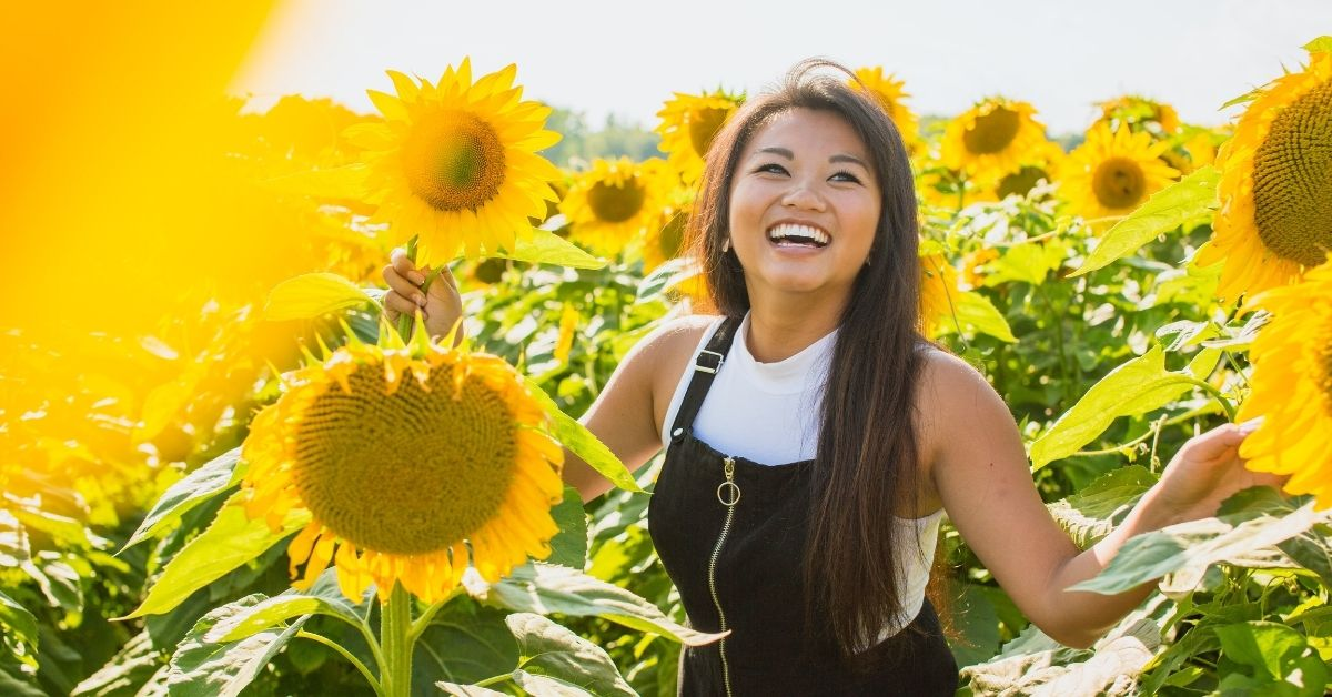 girl smiles standing in a sunflower field