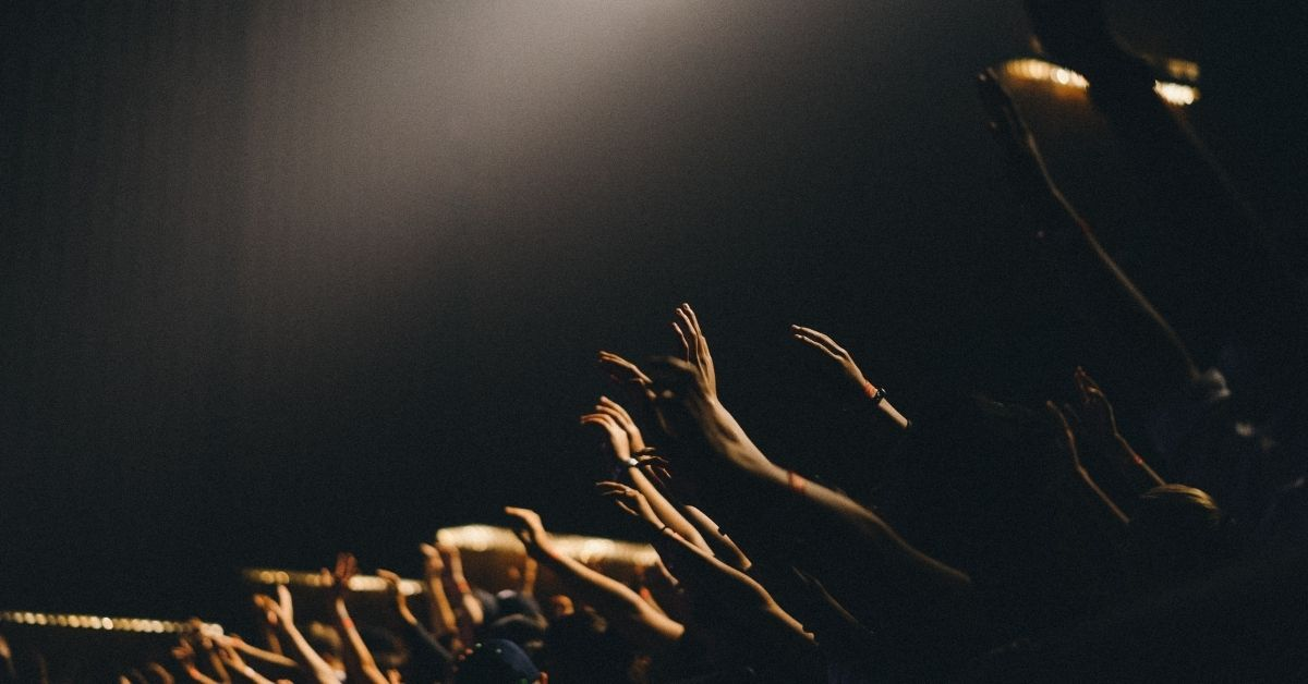 people with hands raised in worship in church