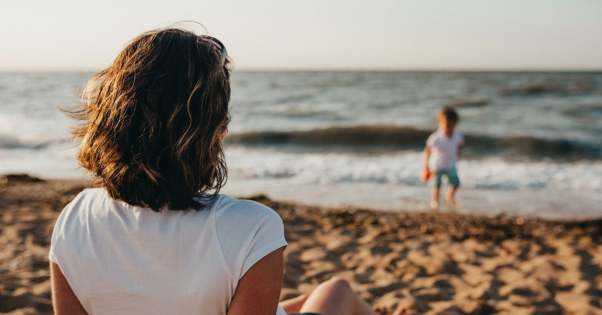 a mum watches her son play at the beach