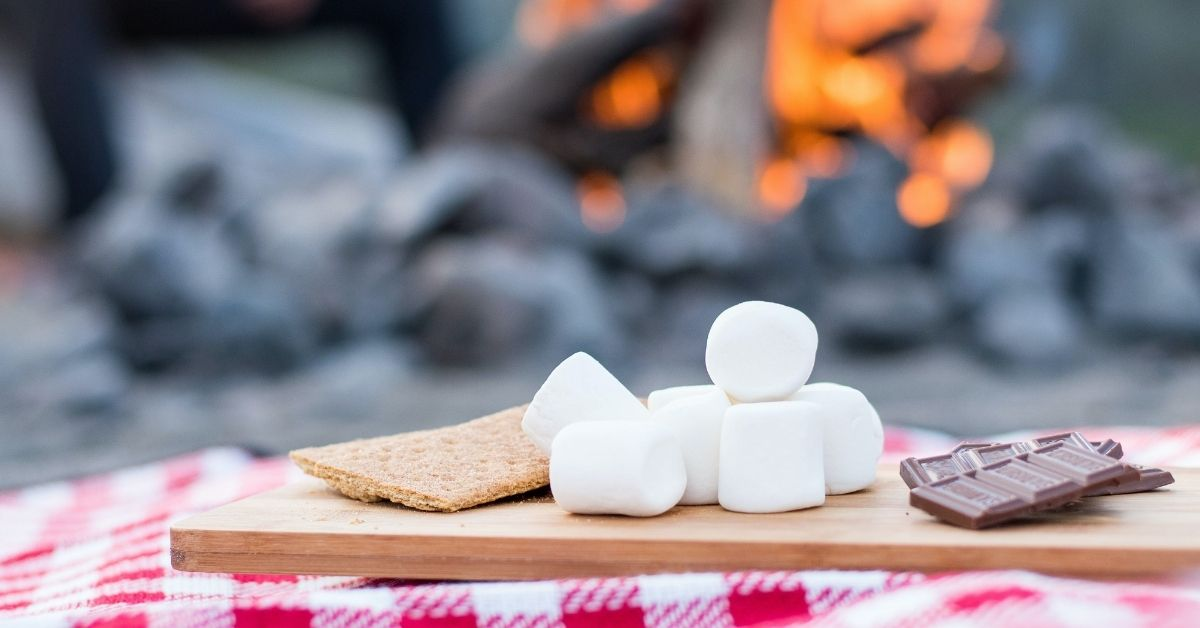 ingredients for smores in front of a campfire - biscuits, marshmallows and chocolate