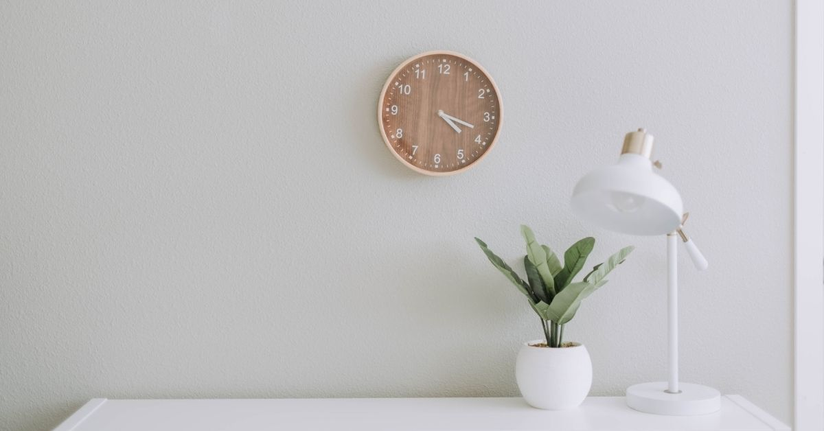 a minimalistic fresh white workspace with a clock, plant, desk and lamp