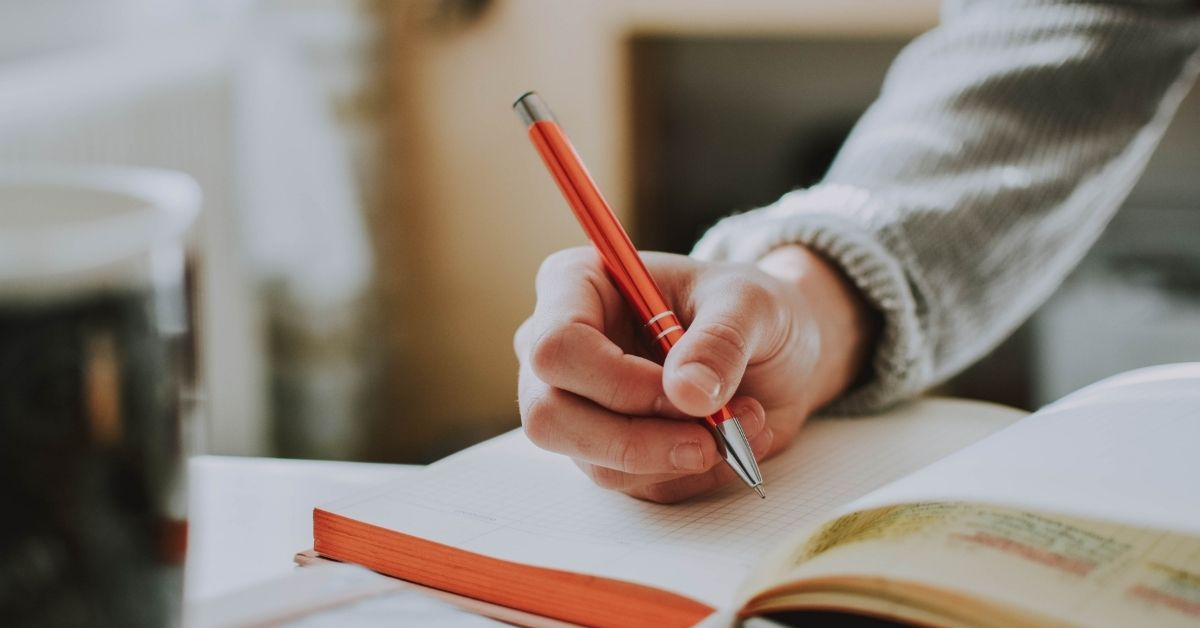 a woman writes in a journal with a red pen