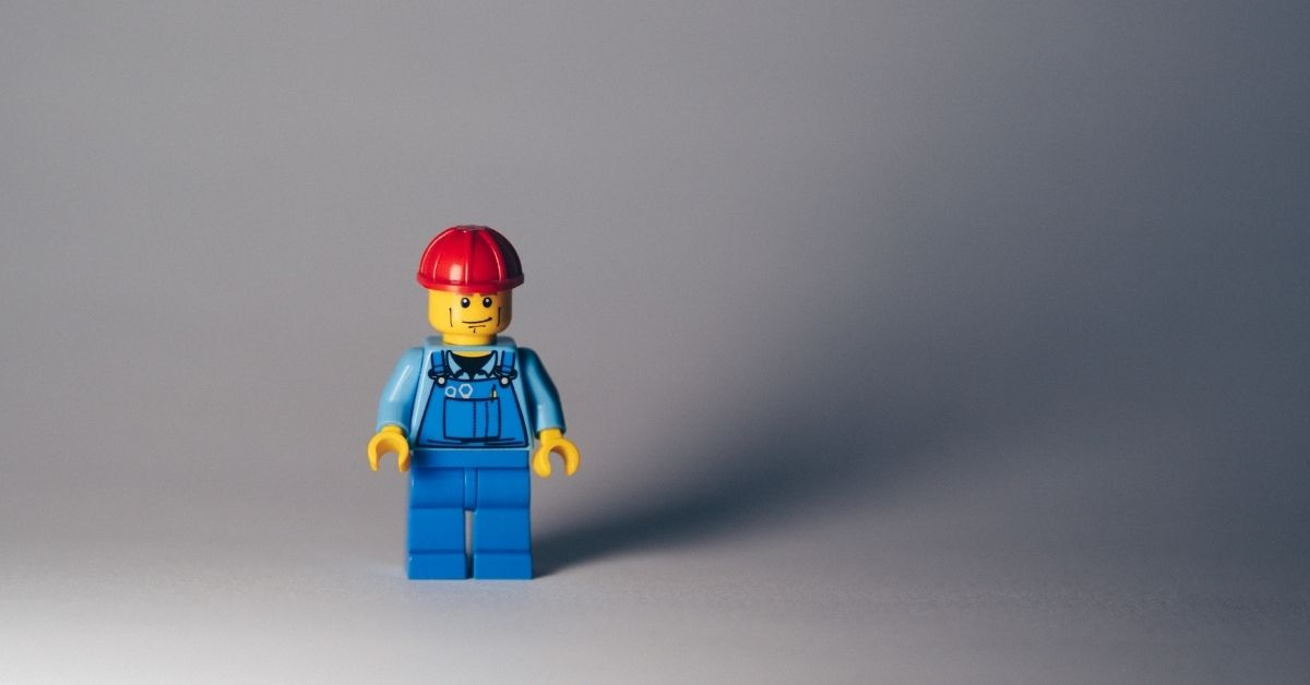 a lego man in blue overalls and a red hard hat