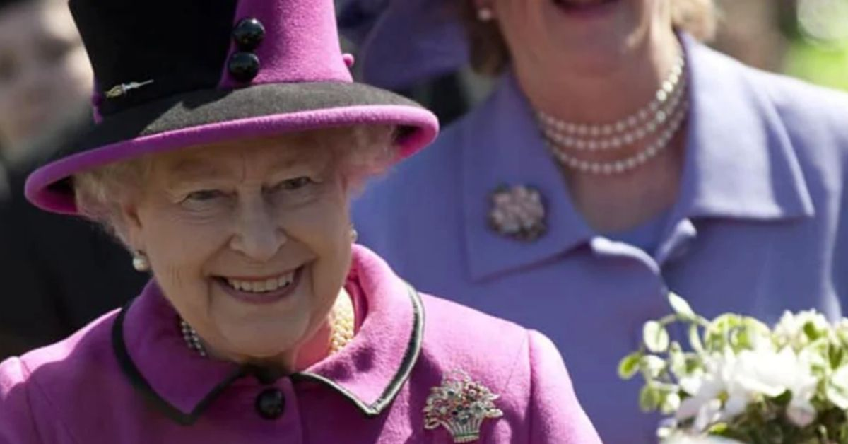 the queen in her purple outfit smiling as she walks ahead