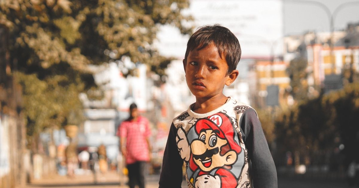 a young boy of middle eastern appearance stands in a street