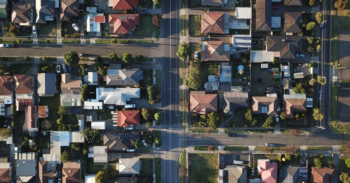 an aerial photo of a suburb during the afternoon with the sun casting shadows across the streets