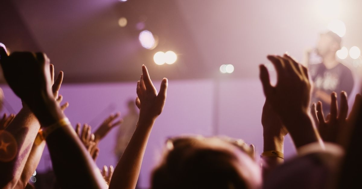 a crowd claps for a performer
