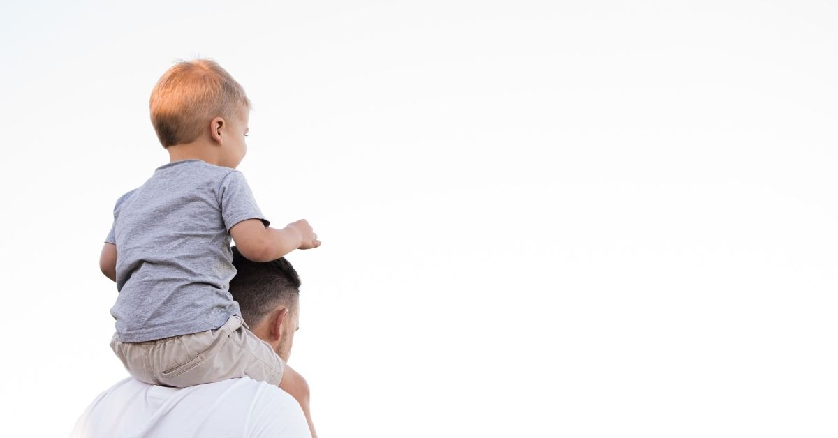 a boy sits on his father's shoulders