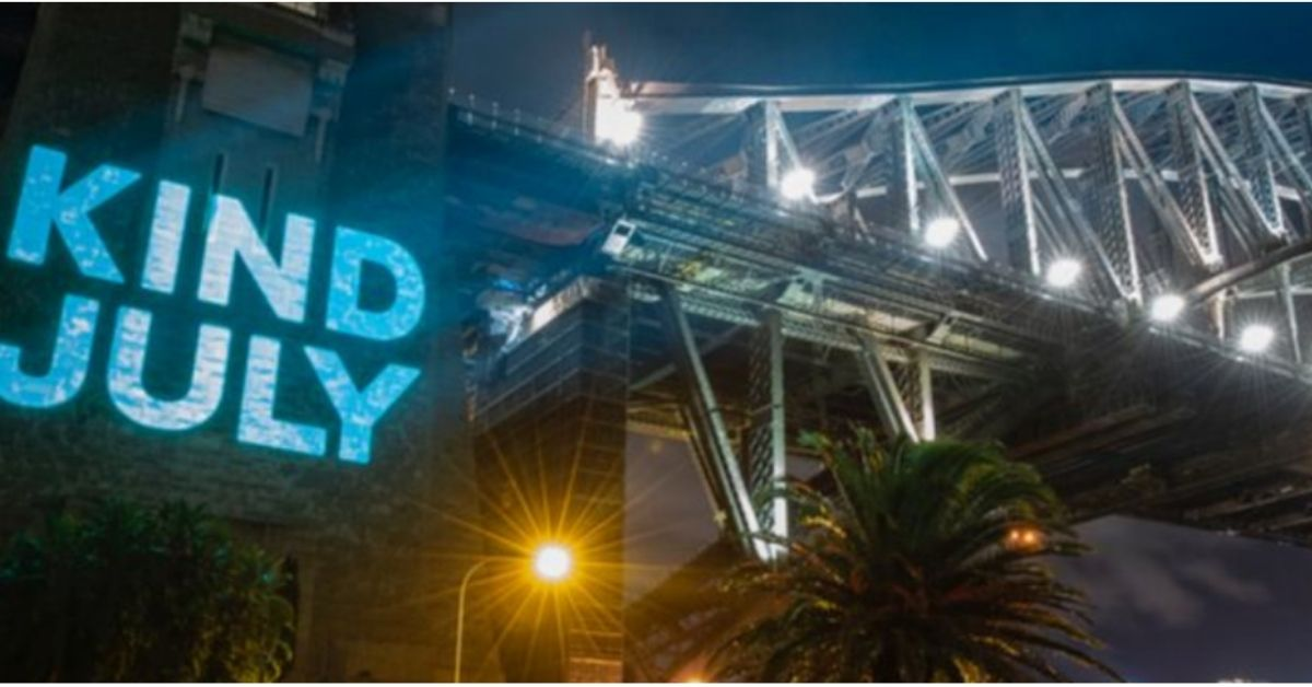 big neon sign saying kind july on the side of the sydney harbour bridge
