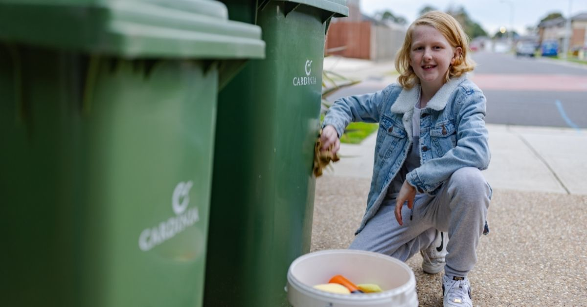 curtis with cleaning supplies kneeling bside two green wheelie bins