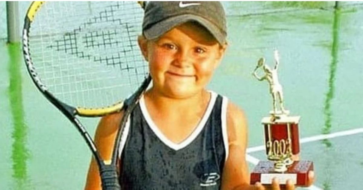 young ash barty holding a racquet and trophy