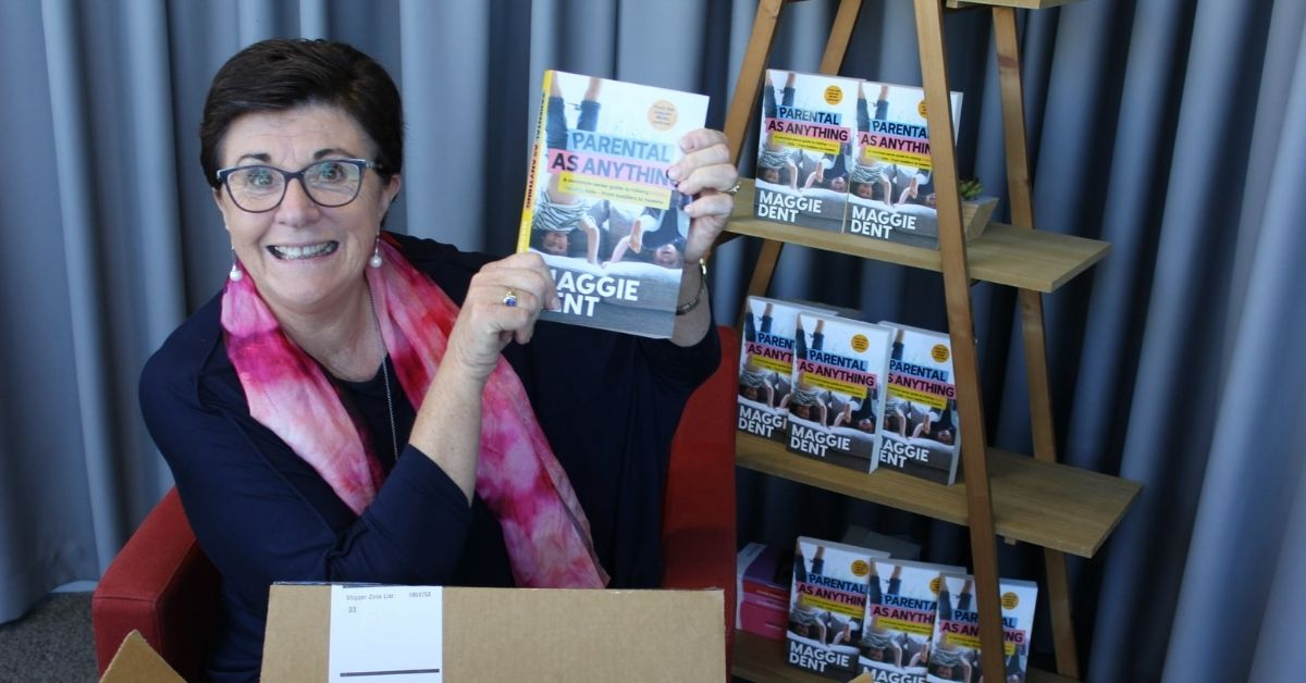 maggie dent holding a copy of her book parental as anything